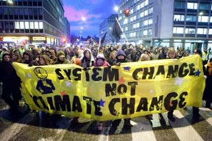 System Change Not Climate Change banner at street march