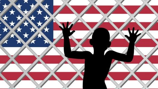 Silhouette of a child up peering through a fence at the U.S. border